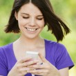 Young smiling woman with mobile phone — Stock Photo