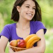Young smiling woman holding basket with fruits — Stock Photo #6068591