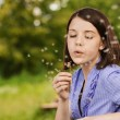 Young woman blowing on dandelion — Stock Photo