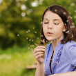 Young woman blowing on dandelion — Stock Photo #6068596