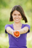 Young cheerful woman holding tomato — Stock Photo