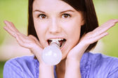 Portrait of young funny woman with bulb in mouth — Stock Photo