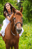 Young brunette woman rides a horse — Stockfoto