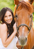 Portrait of young smiling woman with horse — Stockfoto