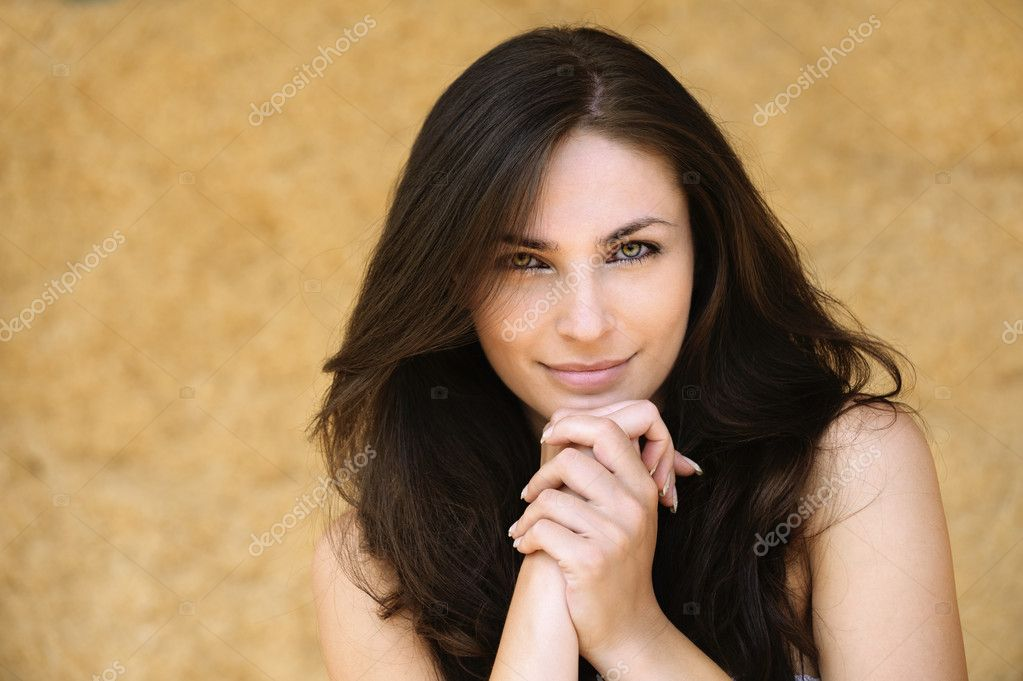 Portrait of young alluring smiling attractive brunnete woman propping up her face against yellow background. — Stock Photo #6084843