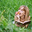 Young woman eating apple and reading book — Stock Photo