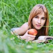 Young woman holding apple and reading book — Stock Photo #6126968