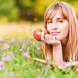 Young woman holding apple and reading book — Stock Photo #6126977