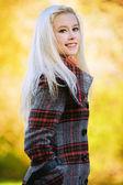 年轻的金发女人在秋天公园 — 图库照片