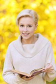 Portrait of smiling blond woman with book — Stock Photo