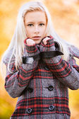 Young appealing blond woman at autumn park — Stock Photo