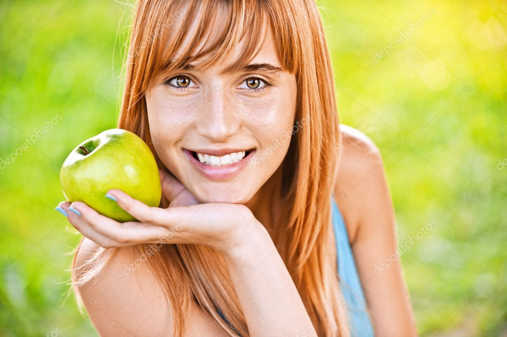 Close-up portrait of young attractive woman holding an apple, propping up her face and smiling at summer green park. — Stock Photo #6126984