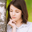 Portrait of young brunette near birch tree - Stock Photo