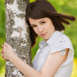Portrait of young dark-haired woman embracing birch tree — Stock Photo #6142943