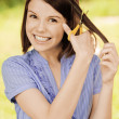 Portrait of brunette woman cutting her hair - Stock Photo