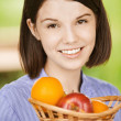 Royalty-Free Stock Photo: Portrait of young smiling brunette holding basket with fruits