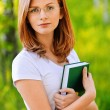 Stock Photo: Portrait of young woman with book