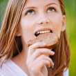 Portrait of beautiful young woman eating bread — Stock Photo