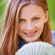 Portrait of young woman holding much money - Stock Photo