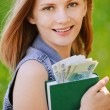 Portrait of smiling woman holding a book with money - Stock Photo