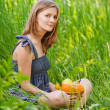 Portrait of young woman sitting in grass with basket full with f — Stock Photo