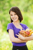 Portrait of young happy woman holding basket with juicy fruits — Stock Photo