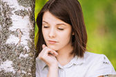 Portrait of young brunette near birch tree — Stock Photo