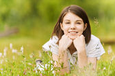 Teen girl lying on grass — Stockfoto
