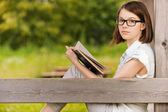 Portrait of young witty woman with book — Stock Photo