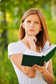 Young thoughtful woman holding book — Stock Photo