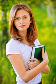 Portrait of young woman with book — Stockfoto