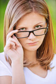 Portrait of strict woman looking above her glasses — Stock Photo
