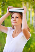 Portrait of young woman holding books on her head — Stock Photo