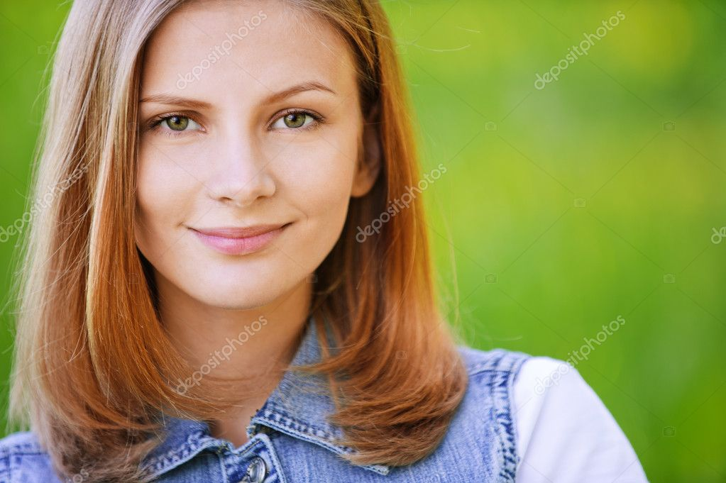 Close-up portrait of young attractive beautiful fair-haired woman wearing jean jacket at summer green park. — Stock Photo #6145573