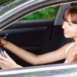 Portrait of young smiling woman driving car — Stock Photo