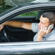 Young man speaking on telephone and driving car - Stock Photo
