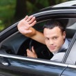 Portrait of young man driving car and greeting somebody with han - Stok fotoğraf