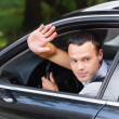 Portrait of young man driving car and greeting somebody with han - Stock Photo