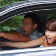 Young couple driving car - Stock Photo