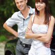 Two young smiling near car - Stock Photo