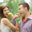 Two young happy eating apples - Stock Photo