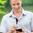 Young man holding smartphone — Stock Photo