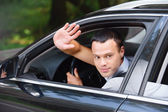 Portrait of young man driving car and greeting somebody with han — Stok fotoğraf