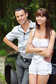 Two young smiling near car — Stock Photo