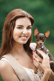 Portrait of young smiling woman holding dog — Stock Photo