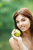 Beautiful smiling woman holding green apple — Stock Photo