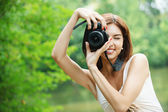 Portrait of young smiling woman taking photo — Stock Photo
