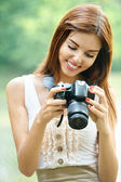 Portrait of young beautiful brunette woman holding photocamera — Stock Photo