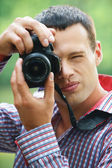 Young man taking photos — Stock Photo