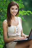 Beautiful smiling woman working with laptop — Stok fotoğraf